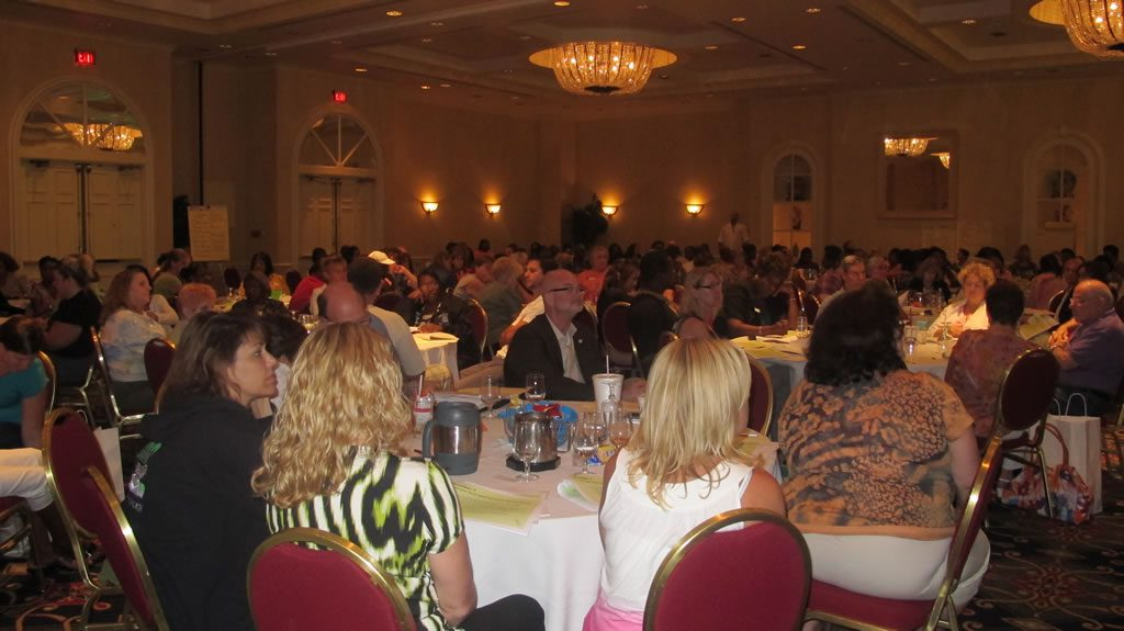 Hall full of tables of people at annual conference