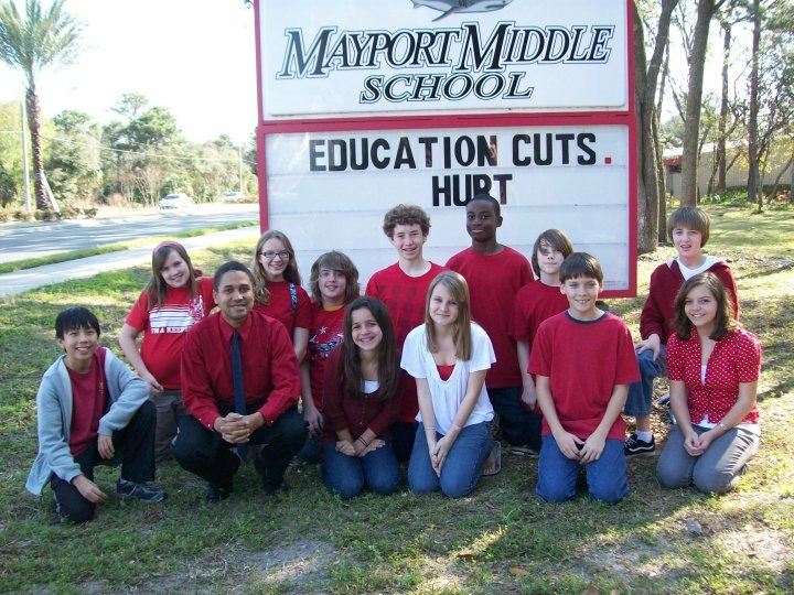 John Meeks and students in front of Mayport Middle School sign